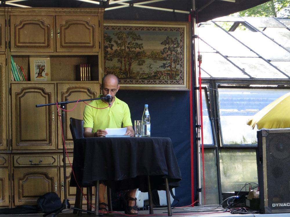 Issam Alnajm liest aus einem Manuskript