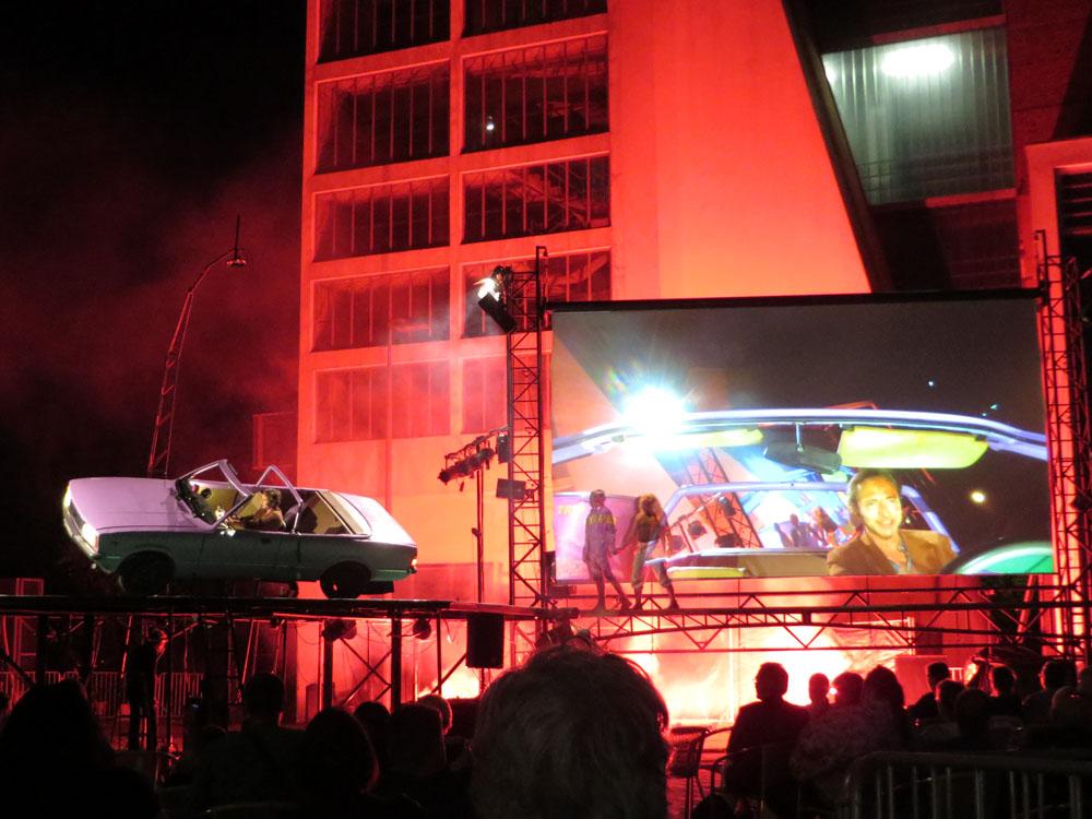 In rotes Licht getauchte Bühne mit altem Ford Mustang und Videoprojektion