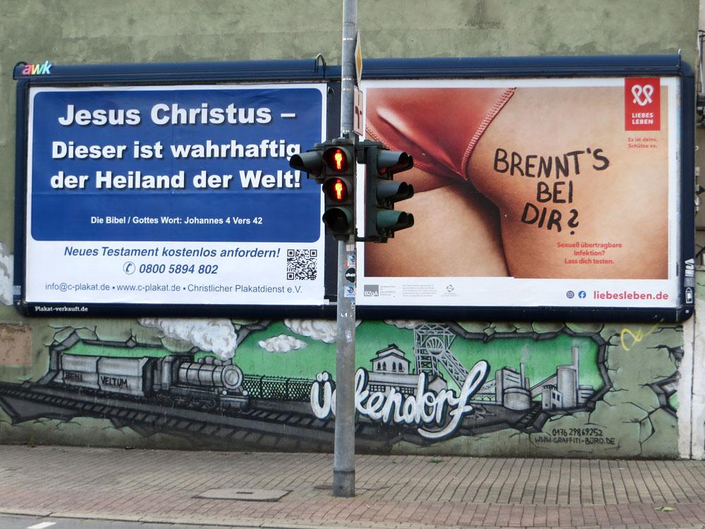 """Zwei Plakate nebeneinander: """"Jesus Christus – Dieser ist wahrhaftig der Heiland der Welt!"""" und """"Brennt's bei Dir? Sexuell übertragbare Infektion? ..."""""""